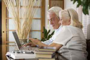 A happy elderly couple using a computer